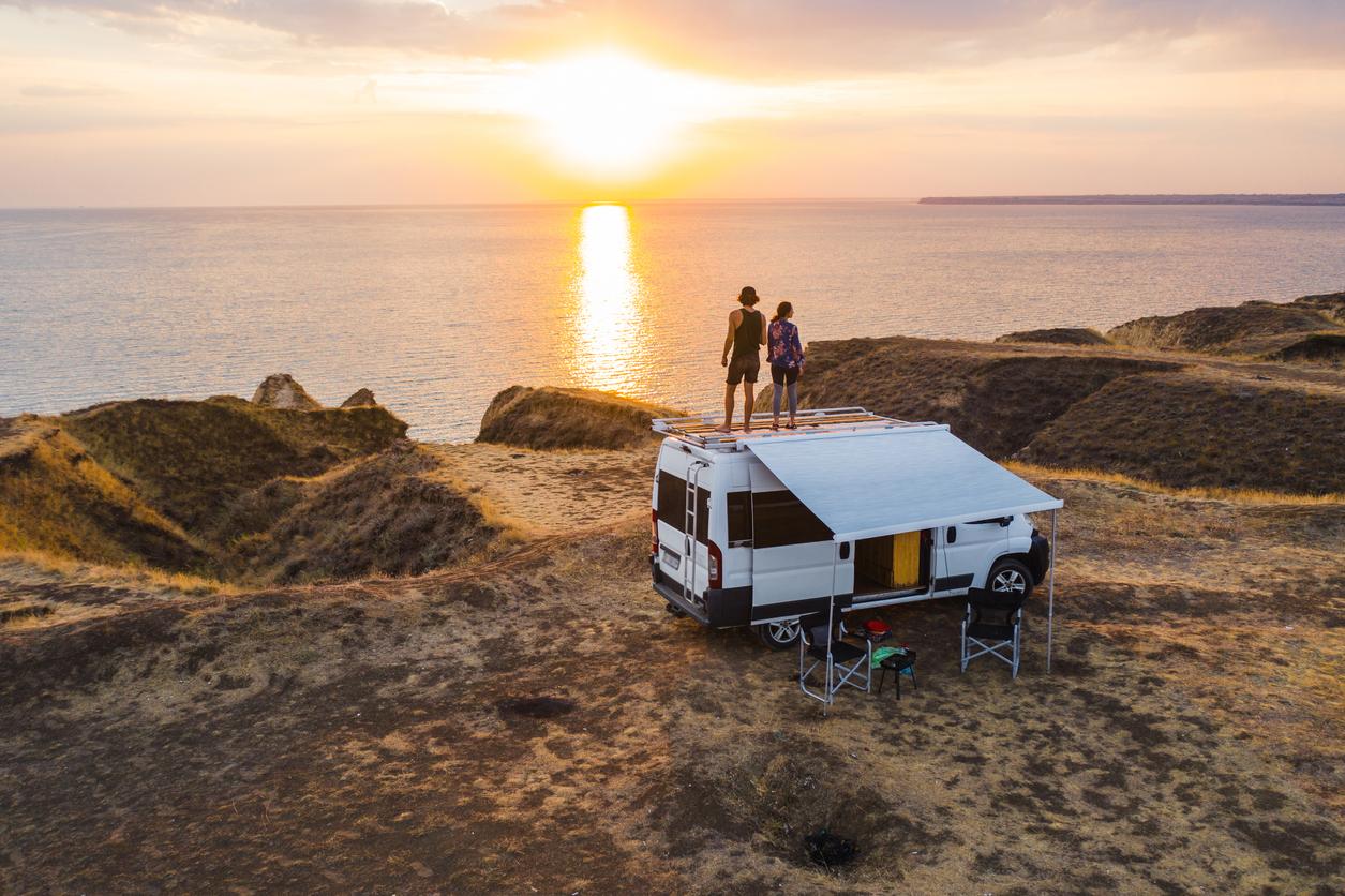 Aerial view of heterosexual couple on roof of camper van on seaside  at sunset